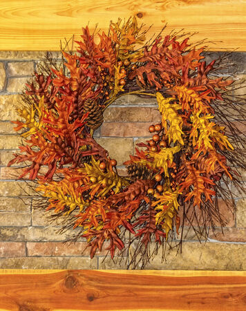 stone  fireplace: Large autumn wreath against a stone fireplace and wooden mantle.