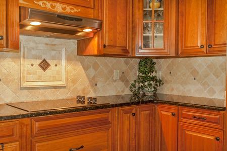 Traditional kitchen with stone backsplash and granite countertop Stockfoto