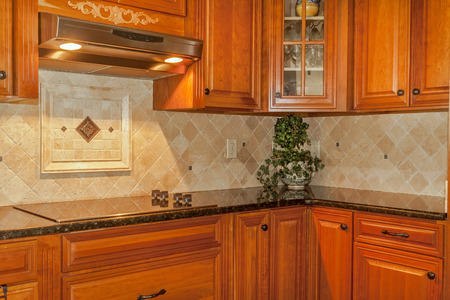 Traditional kitchen with stone backsplash and granite countertop Standard-Bild