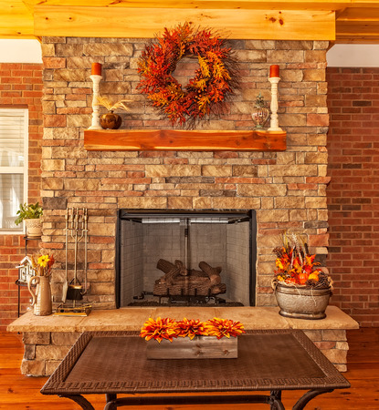 stone fireplace: Covered backyard deck at residential house with gas fireplace, decorations for the season of autumn.