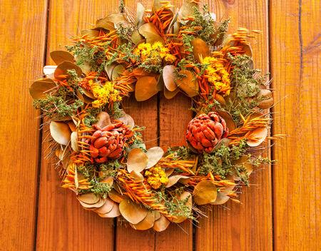 fiori secchi: Corona di autunno con fiori secchi su uno sfondo di legno Archivio Fotografico