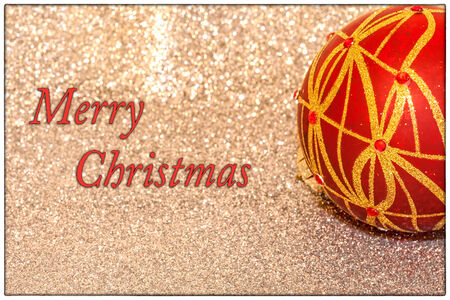 A Merry Christmas card, with text, and a red ornament ball with sparkly background Stock Photo