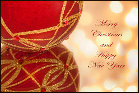 A Merry Christmas card, with text, and a red ornament ball with soft bokeh lights in background Stock Photo