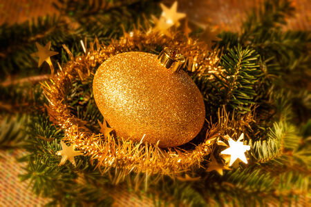 Gold Christmas ornament with spruce and tinsel.