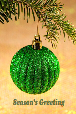 Seasons Greeting card with green sparkly ornament on Christmas tree with soft background
