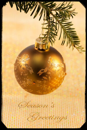 happy holidays text: Gold Christmas ornament hanging from Christmas tree with Happy Holidays text and gold background
