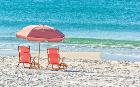 destin: Pink umbrella and lounge chairs on the Miramar Beach in Destin, Florida