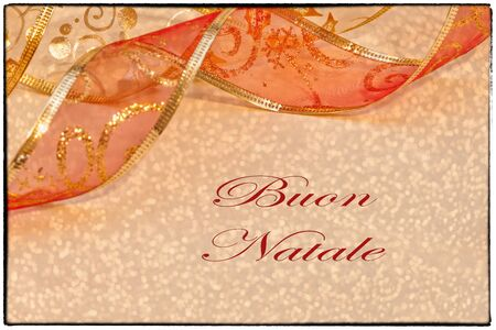 buon: Merry Christmas card, in Italian, with red and gold ribbon and soft lights background