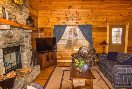 Interior of Log Cabin, with stone fireplace and seating area