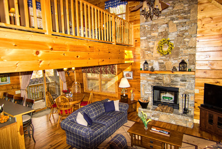 seating area: Interior of Log Cabin, with stone fireplace, seating area and loft Stock Photo