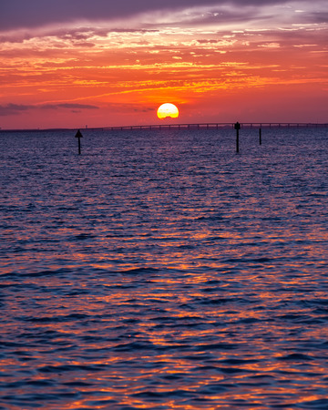 destin: Sun setting over the horizon and the Gulf of Mexico in Destin, Florida