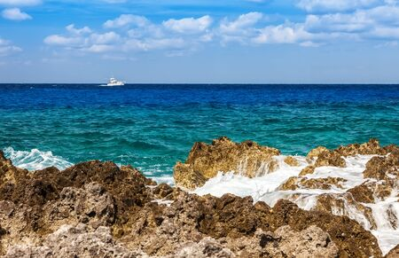 cayman: Fishing boat on the Caribbean along the rocky shoreline of Grand Cayman, Cayman Islands.