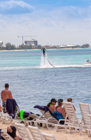 mile: Grand Cayman, Cayman Islands - March 8, 2013:  Crowd on beach in Cayman Islands watches an unidentified man using the water Jet Pack on Seven Mile Beach.