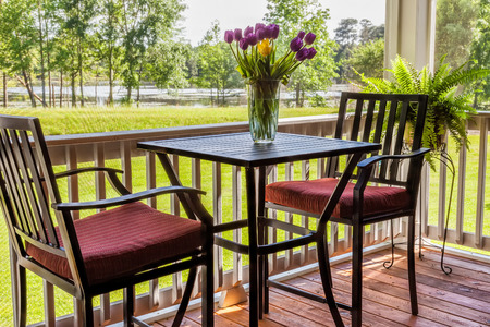 screened: Screened in backyard deck overlooking lake with cafe table and flowers Stock Photo