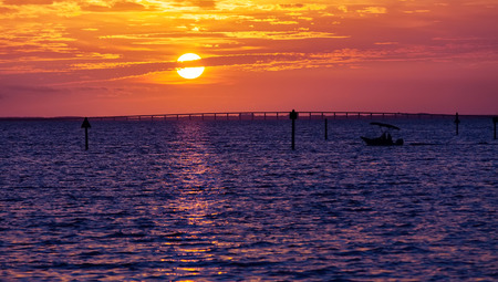 destin: Silhouette of small boat at sunset in Destin, Florida