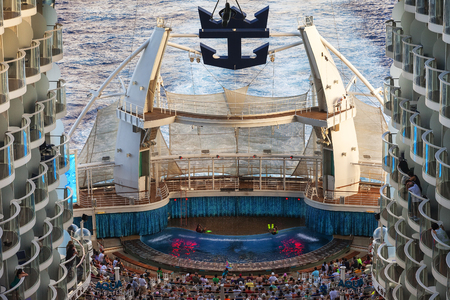 transforms: Caribbean Sea - Jan. 17, 2013: Passengers watch a diving show at the Aqua Theater on the Oasis of the Seas.  It functions as a pool and lounge area by day, and at night it transforms into a theatrical venue with seating for 600 passengers. Editorial
