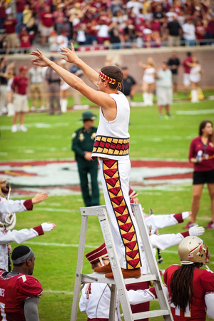 orchestrate: Tallahassee, FL - Nov. 23, 2013:  FSU Band Leader takes the field to orchestrate the music and performance of the Marching Chiefs during a home football game. The band has an average of over 400 students, since th 1980s. Editorial