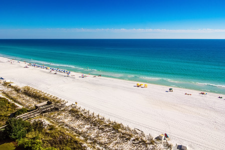 destin: Destin, Florida - Oct. 24, 2014:  Beach goers enjoy the white sandy beaches and emerald blue waters of the panhandle in Destin, Florida. Originating as a small fishing village, it is now a popular tourist destination.