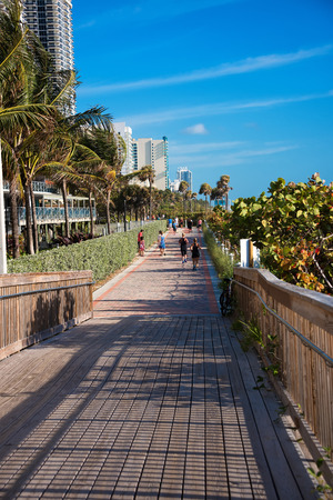 south beach: Miami, FL - March 13, 2015:  Runners and walkers on the Miami Beach Boardwalk in South Beach. The scenic pathway stretches from South Beach and continues north for 40 blocks.  Views of the Atlantic Ocean are on one sdie and luxury resorts are on the other Editorial
