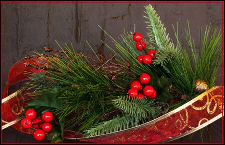 evergreen: Evergreen with holly berries and red ribbon with textured grungy background