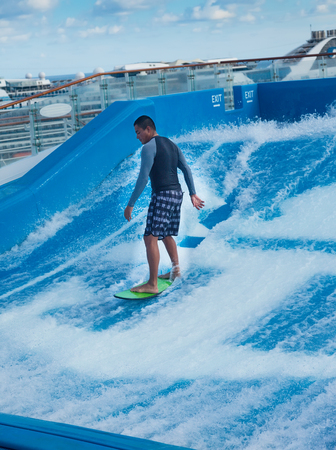 FT. LAUDERDALE, FL - JAN. 12, 2013: Man surfing on the FlowRider aboard the Oasis of the Seas. Royal Caribbean offers this activity to all its guests aboard its Freedom and Oasis-class ships.