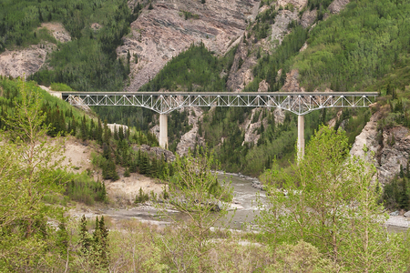 passing over: High bridge passing over a river in the canyons on the Alaskan Mountains