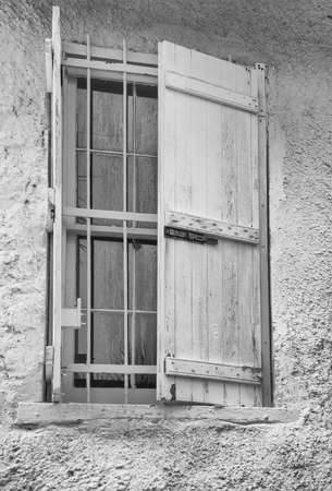 building exteriors: Grungy and textured shutters on an old window in black and white tone