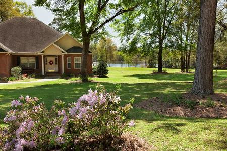 Maison d'habitation sur un lac avec grande cour au printemps Banque d'images - 57221376