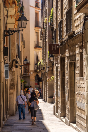 Barcelona, Spain - June 19, 2016:  Pedestrians walk along one of many narrow alleyways that meander throughout the city Barcelona, Spain.