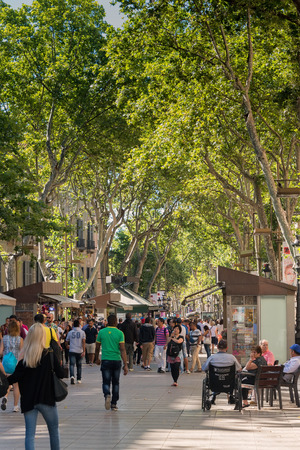 ramblas: Barcelona, Spain -June 19, 2016:  People fill the tree lined pedestrian mall in Barcelona, named Las Ramblas. Its 1.2 kilometers long and filled with stores, restaurants and theaters for tourists to see.