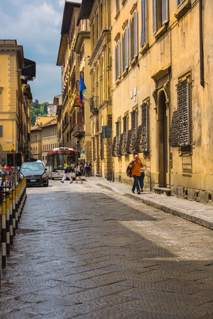 maneuver: Florence, Italy - June 9, 2016:  Pedestrians and cars maneuver down narrow European style streets and historical architecture in Florence, Italy.