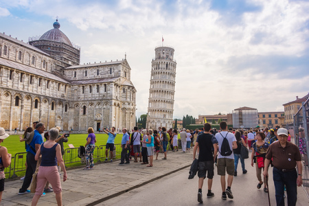 Pisa, Italy - June 9, 2016:  Tourists gather in the Square of Miracles in Pisa to see the Leaning Tower of Pisa and the medieval cathedral of the Archdiocese of Pisa.