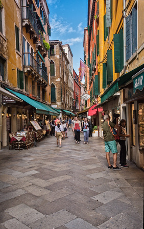 Venice, Italy - June 13, 2016:  People stroll down one of the many narrow shopping alleyways, usually filled with shops, restaurants and hotels.