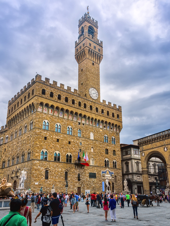 Florence, Italy - June 9, 2016:  Tourists gather to admire the statues in the Palazzo Vecchio, which houses the town hall of Florence. The massive building is enhanced by the simple tower with its clock, and its copy of Michelangelos David statue. Editorial