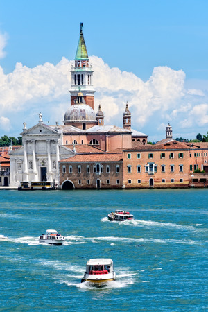 Church of the Most Holy Redeemer in Venice, Italy with water taxis in the lagoons harbor.