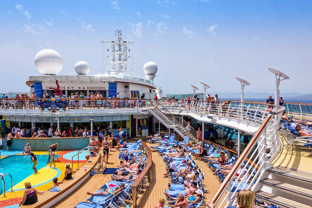 Mediterranean Sea - June 17, 2016:  Passengers aboard Royal Caribbean's Brillance of the Seas relaxing by the pool during a day at sea. Standard-Bild