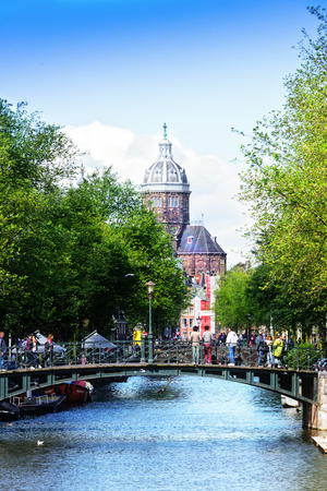 Amsterdam, Netherlands - July 12, 2017:  Pedestrians walking in Amsterdam, known for its artistic heritage, numerous canal system and narrow houses with gabled facades.