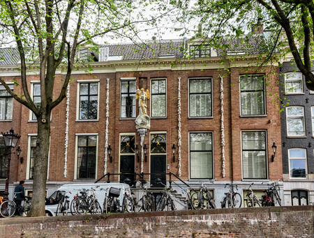Amsterdam, Netherlands - July 14, 2017:  Closely constructed houses with artistic heritage and gabled facades along the many water canals in Amsterdam. Editorial