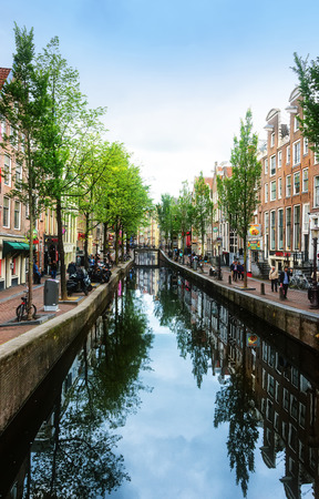 Amsterdam, Netherlands - JUly 13, 2017:  Pedestrians walking in Amsterdam, known for its artistic heritage, numerous canal system and narrow houses with gabled facades.