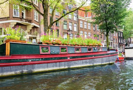 Grote woonboot verankerd op een kanaal in de hoofdstad van Amsterdam Stockfoto