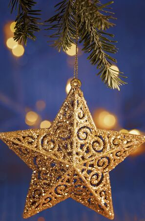Gold star christmas tree ornament hanging from branch with soft lights in the background Stock Photo