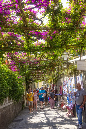 Positano, Italy - June 11, 2016:  Flowering alleyways filled with shoppers and tourists during warm summer day.