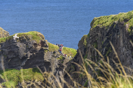 County Antrim, Northern Ireland - August 10, 2018:  Tourists take the long walk across the Carrick-a-Rede Rope Bridge near the Giants Causeway in Northern Ireland. Editorial