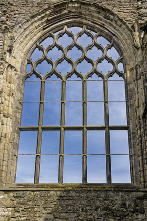 Stone wall window frame with blue skies inside the Holyrood Abbey, Edinburgh, Scotland