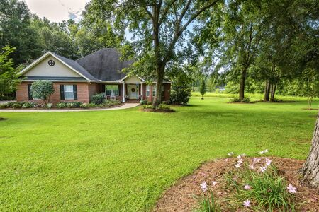 Brick colonial house with nicely landscaped yard and lake in background