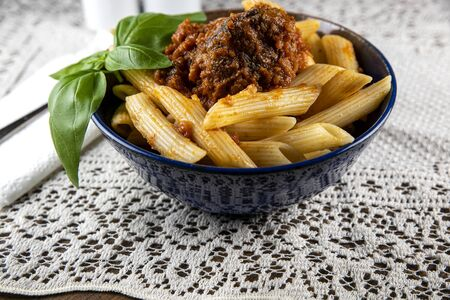 Bowl of homemade ziti pasta on a lace placemat with a spig of basil Archivio Fotografico