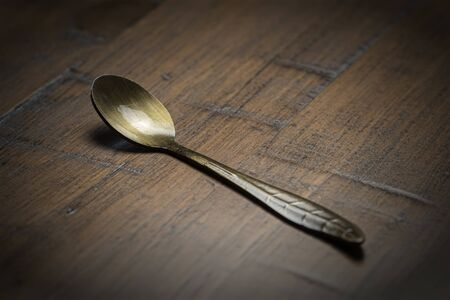 Old tarnished vintage spoon on a wooden table