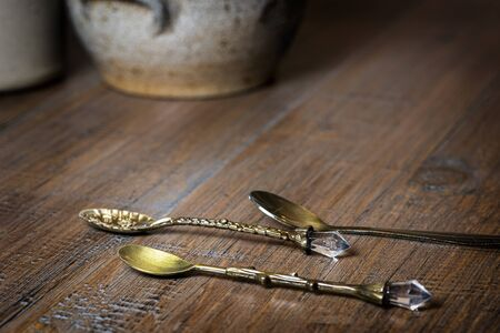 Old vintage spoons on a wooden table with pottery in background
