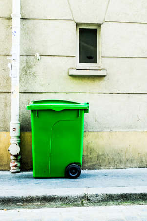 greem: Green garbage outside a building in Paris Stock Photo