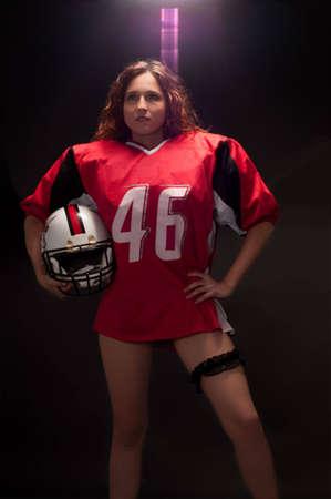 Sexy American football player holding a helmet under a spotlight  Stock Photo